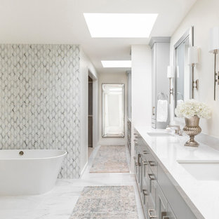 This is an example of a traditional bathroom in Houston with recessed-panel cabinets, grey cabinets, a freestanding bath, grey tiles, white tiles, white walls, a submerged sink, white floors and white worktops.
