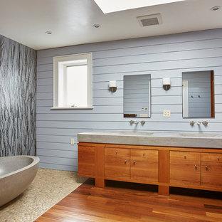 Imagen de cuarto de baño principal, contemporáneo, con armarios con paneles lisos, puertas de armario de madera oscura, bañera exenta, paredes azules, suelo de baldosas tipo guijarro, lavabo integrado y encimera de cemento