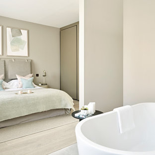 Medium sized contemporary ensuite bathroom in London with grey walls and a freestanding bath.