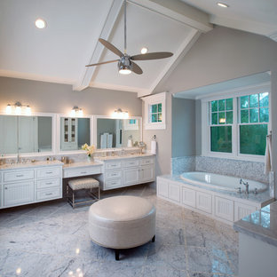 Foto de cuarto de baño principal, tradicional, grande, con puertas de armario blancas, bañera encastrada, lavabo bajoencimera, armarios con rebordes decorativos, encimera de mármol, baldosas y/o azulejos blancos, baldosas y/o azulejos de piedra, paredes grises y suelo de mármol