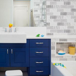 Ejemplo de cuarto de baño infantil, tradicional renovado, de tamaño medio, con puertas de armario azules, bañera empotrada, combinación de ducha y bañera, baldosas y/o azulejos blancas y negros, baldosas y/o azulejos de cemento, paredes multicolor, lavabo encastrado, encimera de cuarzo compacto, suelo gris, ducha con cortina, encimeras blancas y armarios estilo shaker