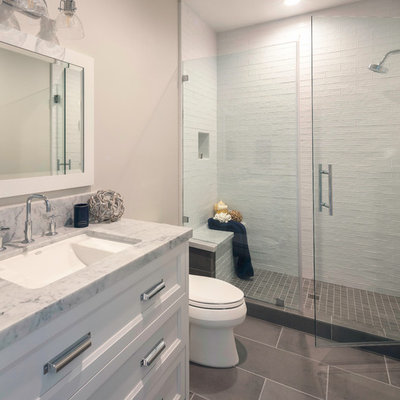 Corner shower - mid-sized country kids' gray tile and ceramic tile ceramic tile and gray floor corner shower idea in San Francisco with shaker cabinets, white cabinets, a two-piece toilet, gray walls, an undermount sink, marble countertops, a hinged shower door and gray countertops
