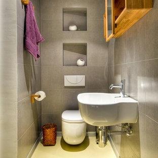 Idee per una stanza da bagno minimal con lavabo sospeso, WC sospeso e pavimento giallo