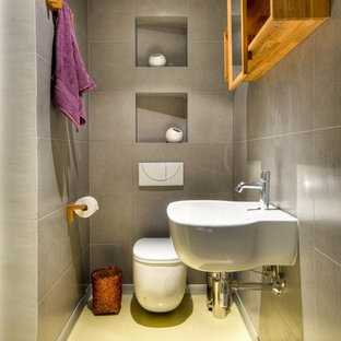 Design ideas for a contemporary bathroom with a wall-mount sink, a wall-mount toilet and yellow floor.