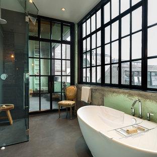 Modelo de cuarto de baño industrial con bañera exenta, ducha esquinera, baldosas y/o azulejos negros, sanitario de una pieza, baldosas y/o azulejos de porcelana, paredes verdes, suelo de cemento y lavabo bajoencimera