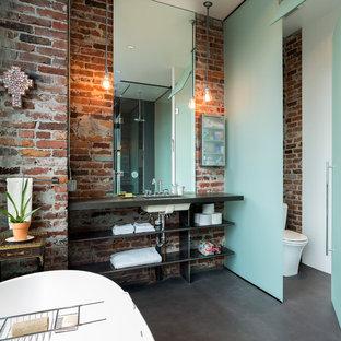 Idee per una stanza da bagno industriale con lavabo sottopiano, nessun'anta, vasca freestanding, WC monopezzo, pavimento in cemento e toilette