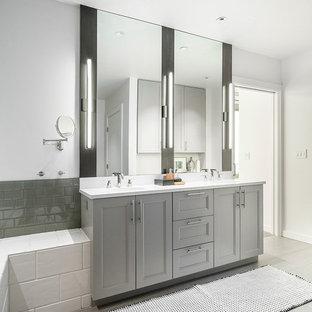 Foto de cuarto de baño principal, urbano, de tamaño medio, con puertas de armario grises, lavabo bajoencimera, encimera de cuarzo compacto, encimeras blancas, armarios con paneles empotrados, baldosas y/o azulejos grises, baldosas y/o azulejos de cemento, paredes blancas y suelo gris