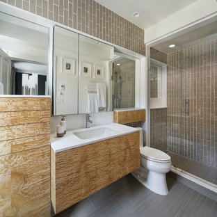 Example of a small minimalist 3/4 beige tile and ceramic tile porcelain floor alcove shower design in Boston with an undermount sink, flat-panel cabinets, medium tone wood cabinets, solid surface countertops, a one-piece toilet and beige walls