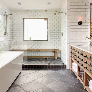 Diseño de cuarto de baño principal, de estilo de casa de campo, grande, con armarios tipo mueble, puertas de armario de madera clara, bañera exenta, ducha doble, baldosas y/o azulejos de cemento, paredes blancas, suelo de pizarra, lavabo bajoencimera y ducha con puerta con bisagras