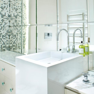 Design ideas for a small contemporary family bathroom in London with a pedestal sink, freestanding cabinets, white cabinets, marble worktops, an alcove shower, a wall mounted toilet, white tiles, mirror tiles, white walls and porcelain flooring.
