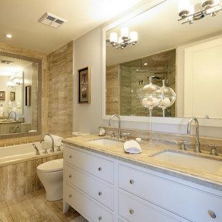 Inspiration for a mid-sized transitional master brown tile and limestone tile alcove bathtub remodel in Toronto with white cabinets, white walls, an undermount sink and beaded inset cabinets