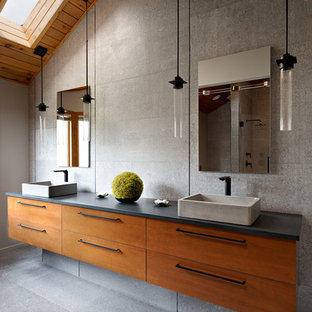 Bathroom - large contemporary master gray tile gray floor and concrete floor bathroom idea in Other with flat-panel cabinets, medium tone wood cabinets, gray walls, a vessel sink, black countertops and concrete countertops