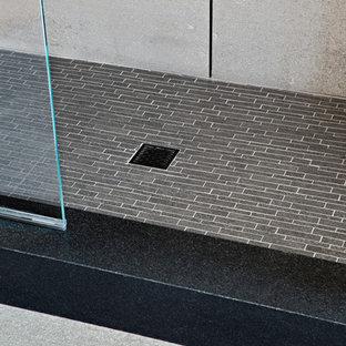 Exempel på ett stort modernt svart svart en-suite badrum, med släta luckor, skåp i mellenmörkt trä, en dubbeldusch, en toalettstol med hel cisternkåpa, grå kakel, grå väggar, ett fristående handfat, grått golv, dusch med gångjärnsdörr, betonggolv och bänkskiva i betong