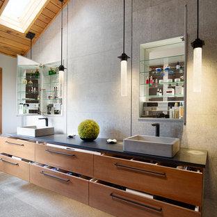 Bild på ett stort funkis svart svart en-suite badrum, med släta luckor, skåp i mellenmörkt trä, en dubbeldusch, en toalettstol med hel cisternkåpa, grå kakel, grå väggar, ett fristående handfat, grått golv, dusch med gångjärnsdörr, betonggolv och bänkskiva i betong