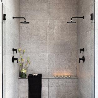 Imagen de cuarto de baño principal, contemporáneo, grande, con ducha doble, baldosas y/o azulejos grises, paredes grises, suelo gris, ducha con puerta con bisagras, armarios con paneles lisos, puertas de armario de madera oscura, baldosas y/o azulejos de cemento, suelo de cemento, lavabo sobreencimera, encimera de cemento y encimeras negras