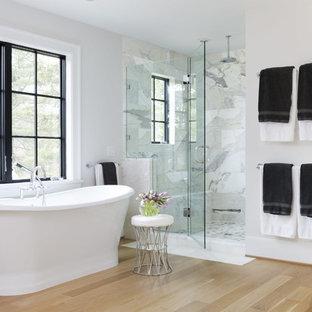 Imagen de cuarto de baño principal, de estilo de casa de campo, grande, con bañera exenta, baldosas y/o azulejos grises, baldosas y/o azulejos de mármol, paredes blancas, ducha con puerta con bisagras, ducha empotrada, suelo de madera en tonos medios y suelo marrón