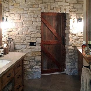 Cette image montre une grande salle de bain principale traditionnelle avec un placard à porte plane, des portes de placard en bois brun, une baignoire en alcôve, un carrelage beige, un sol en carrelage de céramique et un lavabo encastré.