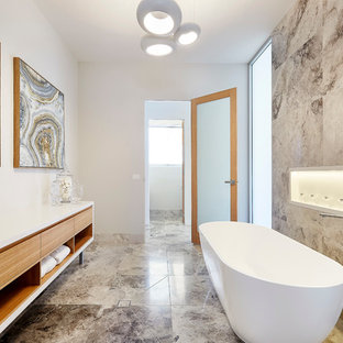 This is an example of an expansive contemporary master bathroom in Sydney with flat-panel cabinets, light wood cabinets, a freestanding tub, gray tile and white walls.
