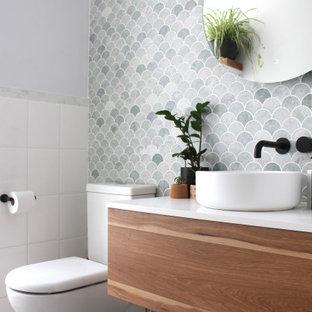 Пример оригинального дизайна: маленькая ванная комната в стиле ретро с фасадами цвета дерева среднего тона, раздельным унитазом, мраморной плиткой, настольной раковиной, столешницей из искусственного кварца, тумбой под одну раковину, подвесной тумбой, плоскими фасадами, серой плиткой, белыми стенами, серым полом и белой столешницей