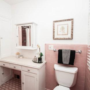 Inredning av ett klassiskt mellanstort vit vitt en-suite badrum, med luckor med infälld panel, vita skåp, en dusch i en alkov, en toalettstol med hel cisternkåpa, rosa kakel, keramikplattor, vita väggar, klinkergolv i keramik, ett piedestal handfat, rosa golv, dusch med duschdraperi och bänkskiva i akrylsten