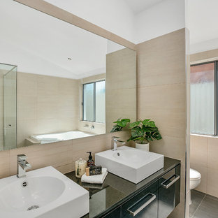 This is an example of a contemporary master bathroom in Gold Coast - Tweed with flat-panel cabinets, black cabinets, a corner tub, a corner shower, beige tile, a vessel sink, black floor, a hinged shower door and black benchtops.