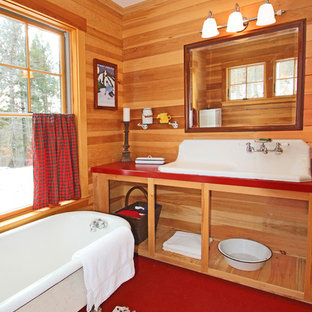 Example of a mid-sized mountain style master terrazzo floor and red floor claw-foot bathtub design in Portland Maine with a trough sink, open cabinets, light wood cabinets and solid surface countertops
