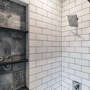 Imagen de cuarto de baño con ducha, industrial, de tamaño medio, con armarios con paneles empotrados, puertas de armario negras, bañera empotrada, combinación de ducha y bañera, sanitario de dos piezas, baldosas y/o azulejos blancos, baldosas y/o azulejos de cemento, paredes blancas, suelo con mosaicos de baldosas, lavabo con pedestal, encimera de acrílico, suelo blanco y ducha con cortina