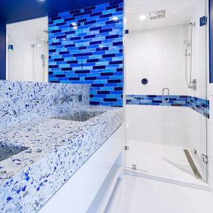 Cette image montre une salle de bain design de taille moyenne avec un carrelage bleu, un carrelage blanc, un carrelage métro, un mur bleu, un lavabo intégré, un placard à porte plane, des portes de placard blanches, un sol en carrelage de porcelaine, un plan de toilette en terrazzo, un sol blanc, une cabine de douche à porte battante et un plan de toilette multicolore.