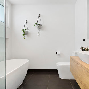 Photo of a contemporary master bathroom in Melbourne with black cabinets, a freestanding tub, white tile, white walls, a vessel sink, wood benchtops, black floor, a hinged shower door and brown benchtops.