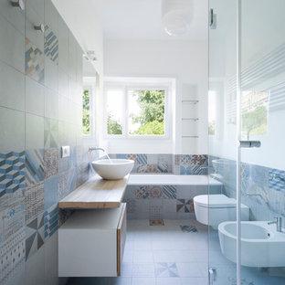 Imagen de cuarto de baño principal, contemporáneo, con lavabo sobreencimera, armarios con paneles lisos, puertas de armario de madera clara, bañera encastrada, bidé, baldosas y/o azulejos de cerámica, suelo de baldosas de cerámica, paredes multicolor y baldosas y/o azulejos multicolor