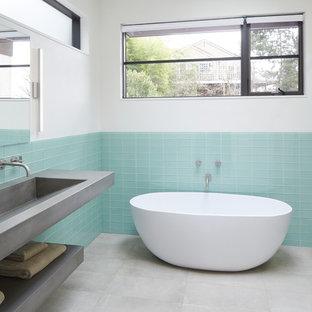 Foto di una stanza da bagno contemporanea con vasca freestanding, doccia alcova, piastrelle blu, piastrelle di vetro, pareti bianche, lavabo rettangolare, pavimento grigio, porta doccia scorrevole e top grigio