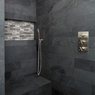 Источник вдохновения для домашнего уюта: главная ванная комната среднего размера в стиле неоклассика (современная классика) с плоскими фасадами, темными деревянными фасадами, угловым душем, унитазом-моноблоком, черной плиткой, плиткой из сланца, серыми стенами, полом из сланца, монолитной раковиной, столешницей из искусственного камня, черным полом, душем с распашными дверями, белой столешницей, сиденьем для душа, тумбой под две раковины и подвесной тумбой