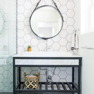 Inspiration for a transitional 3/4 white tile gray floor walk-in shower remodel in Los Angeles with furniture-like cabinets, black cabinets, white walls, a vessel sink, a hinged shower door and white countertops