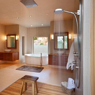 アルバカーキの中くらいのサンタフェスタイルのおしゃれなマスターバスルーム (フラットパネル扉のキャビネット、淡色木目調キャビネット、置き型浴槽、オープン型シャワー、一体型トイレ、磁器タイル、ベージュの壁、淡色無垢フローリング、ベッセル式洗面器、木製洗面台) の写真