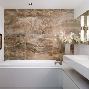 Drop-in bathtub - mid-sized modern master brown tile and stone tile drop-in bathtub idea in Vancouver with white walls, flat-panel cabinets, white cabinets, an undermount sink, engineered quartz countertops and white countertops