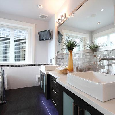 Freestanding bathtub - contemporary black floor freestanding bathtub idea in Vancouver with a vessel sink