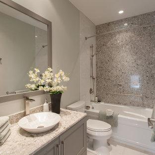 Diseño de cuarto de baño con ducha, de estilo americano, de tamaño medio, con lavabo sobreencimera, armarios estilo shaker, puertas de armario grises, encimera de cuarzo compacto, bañera empotrada, combinación de ducha y bañera, sanitario de una pieza, paredes grises, suelo de baldosas de cerámica y losas de piedra
