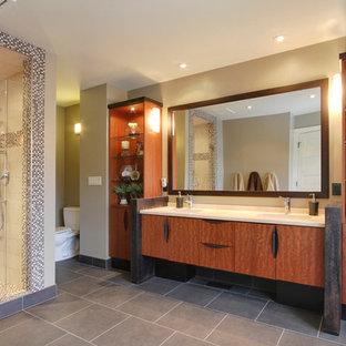カルガリーの巨大なコンテンポラリースタイルのおしゃれなマスターバスルーム (アンダーカウンター洗面器、フラットパネル扉のキャビネット、中間色木目調キャビネット、クオーツストーンの洗面台、置き型浴槽、コーナー設置型シャワー、分離型トイレ、ベージュの壁、セラミックタイルの床) の写真