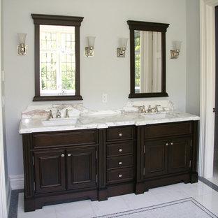 Ispirazione per una stanza da bagno con doccia tradizionale di medie dimensioni con ante con riquadro incassato, ante in legno bruno, vasca freestanding, doccia ad angolo, pareti blu, pavimento in vinile, lavabo sottopiano e top in superficie solida