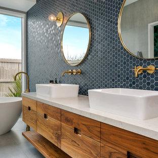 Свежая идея для дизайна: главная ванная комната в современном стиле с отдельно стоящей ванной, настольной раковиной, фасадами островного типа, коричневыми фасадами, душем без бортиков, инсталляцией, синей плиткой, плиткой мозаикой, синими стенами, полом из сланца, мраморной столешницей, коричневым полом и открытым душем - отличное фото интерьера