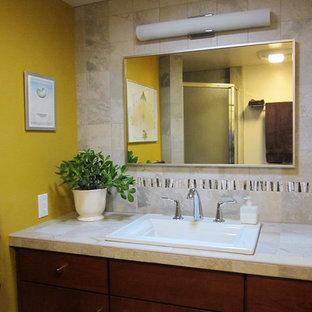 Immagine di una piccola stanza da bagno per bambini tradizionale con ante lisce, ante in legno bruno, piastrelle beige, piastrelle in ceramica, pareti gialle, lavabo da incasso e top piastrellato