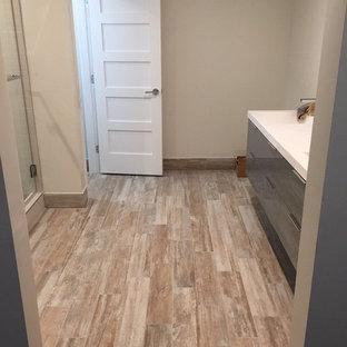 Ejemplo de cuarto de baño principal, de estilo americano, de tamaño medio, con armarios con paneles lisos, puertas de armario grises, ducha empotrada, sanitario de una pieza, baldosas y/o azulejos blancos, suelo de baldosas tipo guijarro, paredes beige, suelo de madera clara, lavabo bajoencimera y encimera de acrílico