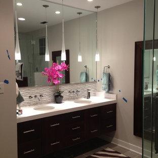 Immagine di una stanza da bagno padronale etnica di medie dimensioni con ante lisce, ante in legno bruno, piastrelle grigie, piastrelle di vetro, pareti beige, pavimento con piastrelle in ceramica, lavabo sottopiano, top in laminato, pavimento grigio e porta doccia a battente
