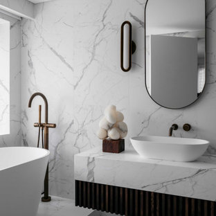 This is an example of a contemporary bathroom in Sydney with dark wood cabinets, a freestanding tub, white tile, a vessel sink, white floor and white benchtops.