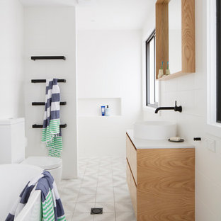 This is an example of a contemporary master bathroom in Brisbane with flat-panel cabinets, light wood cabinets, a freestanding tub, a curbless shower, a two-piece toilet, gray tile, white walls, cement tiles, a vessel sink and an open shower.
