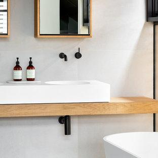 На фото: маленькие ванные комнаты в современном стиле с стеклянными фасадами, отдельно стоящей ванной, открытым душем, белыми стенами, душевой кабиной, подвесной раковиной, столешницей из дерева, открытым душем и коричневой столешницей