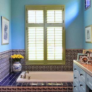 Foto di una grande stanza da bagno mediterranea con ante in stile shaker, ante blu, vasca da incasso, piastrelle blu, piastrelle a mosaico, pareti blu, pavimento in terracotta e pavimento rosso