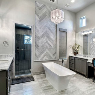 Example of a large transitional master gray tile and stone tile marble floor and gray floor bathroom design in Austin with an undermount sink, shaker cabinets, gray cabinets, marble countertops, gray walls and a hinged shower door