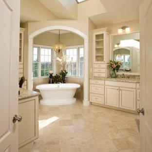 Idee per una grande stanza da bagno padronale classica con ante con riquadro incassato, ante beige, vasca freestanding, WC a due pezzi, piastrelle beige, piastrelle in travertino, pareti beige, pavimento in travertino, lavabo sottopiano, top in granito e pavimento beige