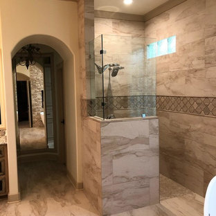 Inspiration for a large mediterranean ensuite bathroom in Houston with a freestanding bath, a built-in shower, brown tiles, ceramic tiles, ceramic flooring, brown floors and an open shower.